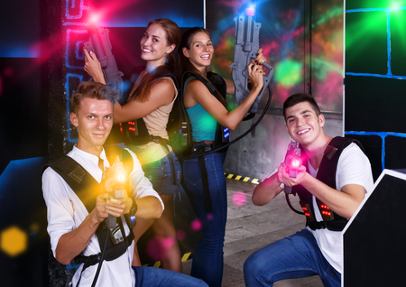 Four positive young male an female posing with laser pistols in their hands in dark laser tag room Reklamní fotografie