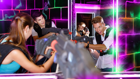 Two happy  smiling laser tag teams playing enthusiastically and aiming at each other in dark room Banco de Imagens