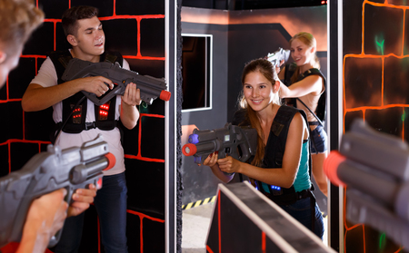 Positive Laser tag players young mens and womens playing in teams in dark laser tag station