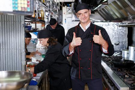 Cheerful cooks dressed in black uniform at restaurant kitchen Stock Photo