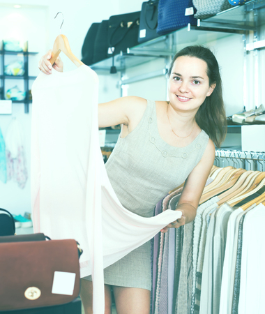 cheerful smiling young female customer looking for pullover at clothing store