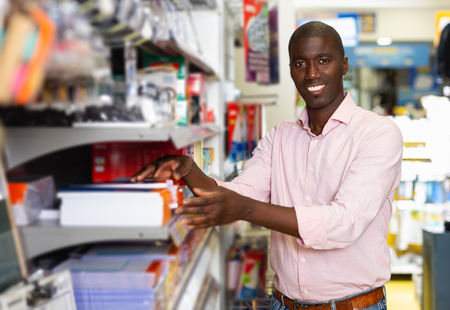 happy African american man  buying office supplies in stationery store Imagens - 120487173