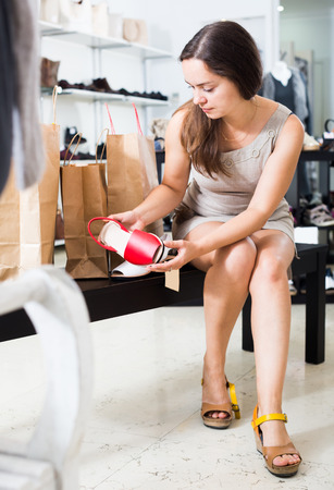 Laughing woman holding bags and smiling in shoes store