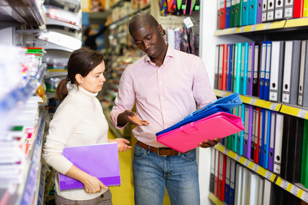 Portrait of glad  positive smiling male and female customers choosing stationery at store