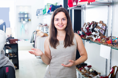 smiling young female seller with dark hair working in shoes store