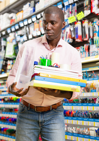 Young male buyer standing with stack of office supplies at a stationery store