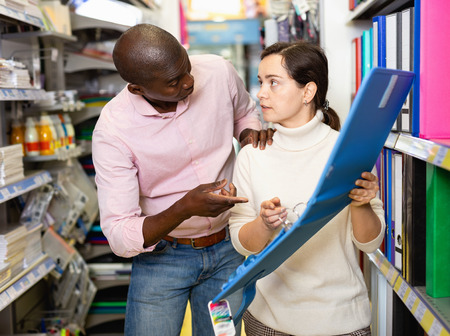 Glad cheerful  couple of  African man and Caucasian woman at stationery shop 写真素材