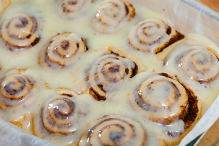 Soft and fluffy cinnamon rolls topped with sugar glaze in baking dish