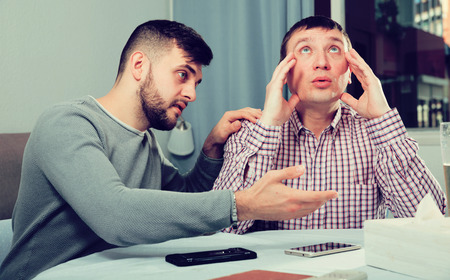 Man comforting his upset friend while discussing problems at table at home