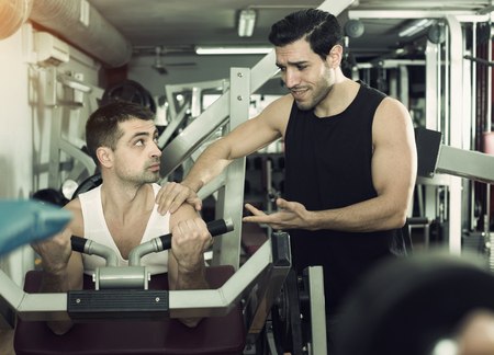 Portrait of sporty man during strength training with personal instructor in gym