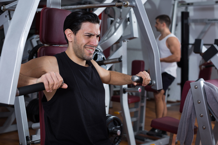 Muscular man doing strength training on fitness machine in modern gym