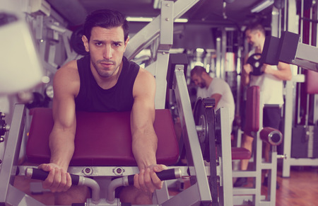 Portrait of athletic man during workout with power exercise machine in gym club
