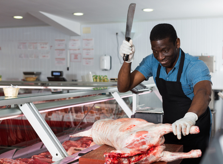 African American male butcher processing carcase of young lamb for sale at butchery Фото со стока