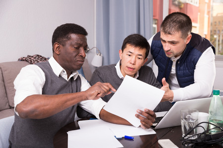 Three seriouse men are working with project and talking about documents together at home.
