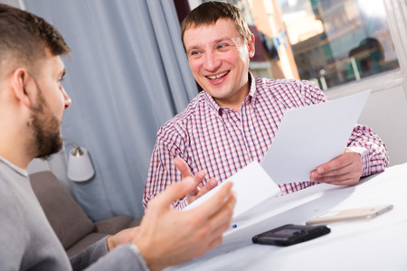 Portrait of cheerful man reading documents together with friend at home table Standard-Bild - 120574297
