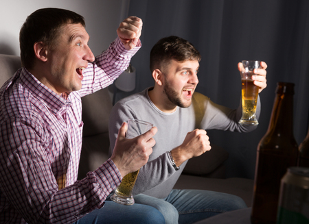 Exalted male friends watching tv together at home, enjoying beer at evening