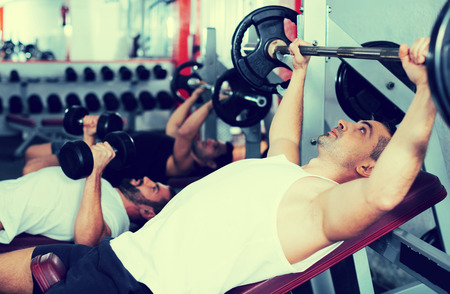 Sporty man performing weightlifting workout at gym, exercising with barbell