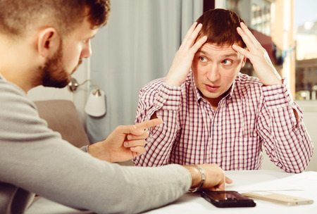 Man having problems with some documents, worriedly discussing with friend at home table