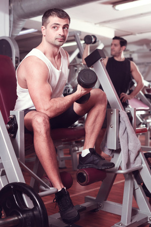 Concentrated sporty guy during workout in gym with dumbbells Stock Photo
