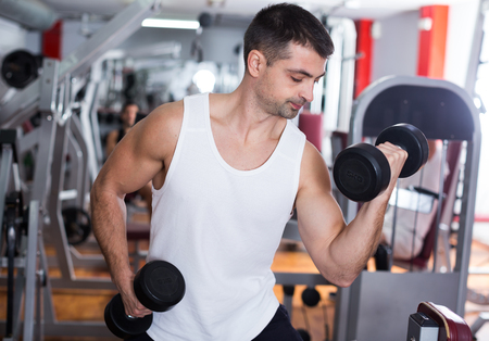Portrait of athletic man exercising with dumbbells in gym Stock Photo