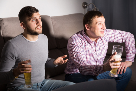 Two men watching matchup on tv with anxious uncertainty while drinking beer together at home