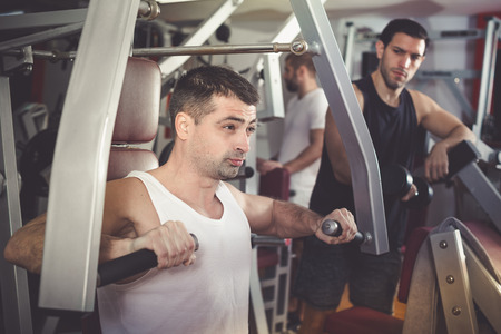 Sporty guy training muscles of arms and shoulder girdle on fitness machine in gym