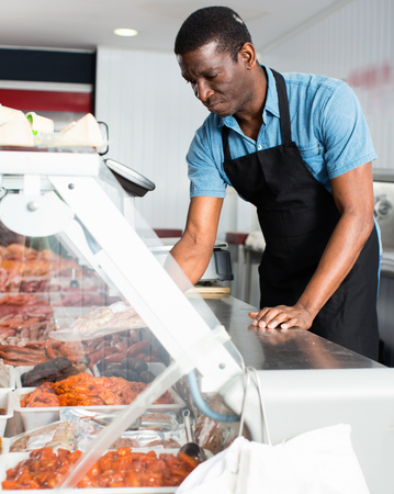 African American glad cheerful positive smiling seller preparing fresh meat of lamb for sale in butcher store