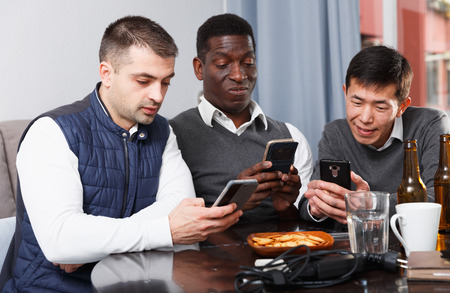Portrait of three men sitting at home table absorbedly looking at phones Standard-Bild - 120427752