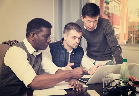 Three serious male friends reading attentively and discussing documents at home Standard-Bild - 120427757