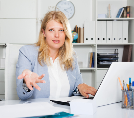 Confident blond female business consultant sitting at workplace and looking at camera