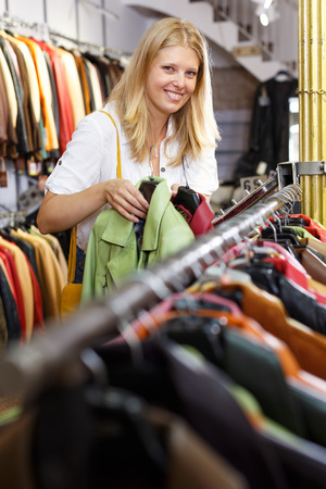 Attractive young blonde choosing leather jacket on racks in clothes store Фото со стока - 120493337