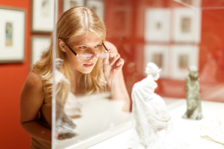 Positive woman with glasses visiting historical museum and looking at showcases with exhibits