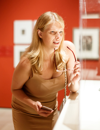 Adult woman with glasses and mobile phone looking at exhibits in glazed stands in art museum Banque d'images