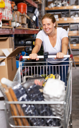 Portrait of positive young female walking with basket of purchases while shopping in building hypermarket Banco de Imagens