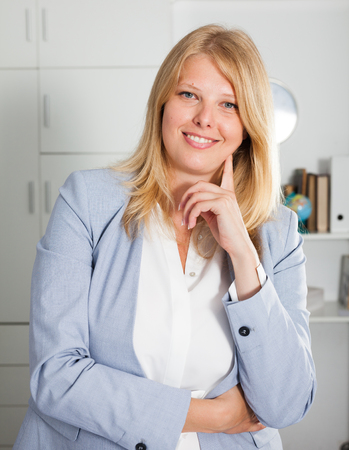 Adult smiling blond woman in business suit standing in modern office