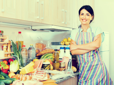 Adult positive smiling woman is posing before cooking on the kitchen at home.