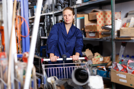 Young positive female worker in uniform with basket of construction  materials walking in the building hypermarket
