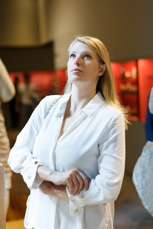 Portrait de jeune femme debout et regardant des objets d'art au musée des arts de l'histoire
