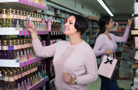 positive woman picking scented spray from shelf in cosmetics store 스톡 콘텐츠