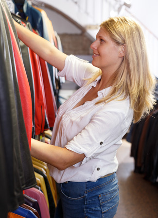 Positive girl looking for new leather jacket during shopping in retail shop