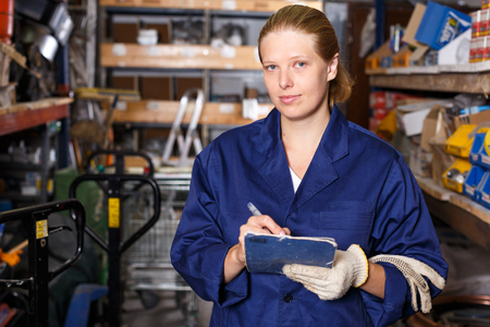 Young female worker holding  notebook and looking construction  materials at shelves in modern build store Stock Photo