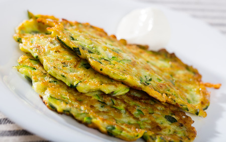 Homemade fritters of courgettes with sour cream sauce