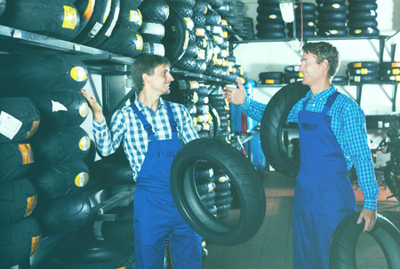 Two coworkers mechanics working with new tires in workshop