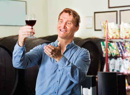 Happy pleasant man wine maker holding wineglass for tasting in wine house