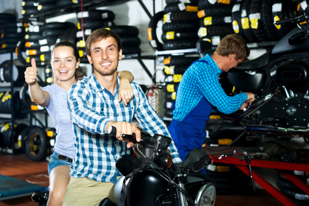 Young cheerful couple sitting on motorcycle at service point Stock Photo