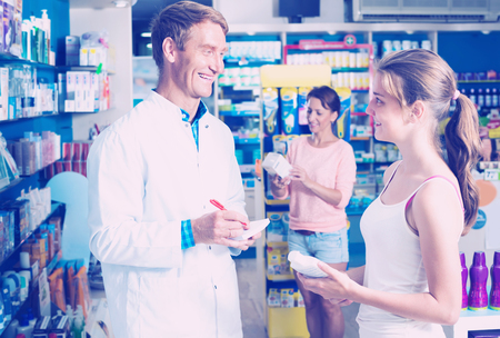 friendly man pharmacist in white uniform helping customers in pharmaceutical shop Imagens