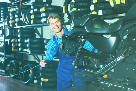 caucasian man in coveralls checking motorcycle in workshop Foto de archivo