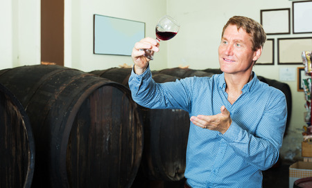 Smiling man sommelier showing glass of wine in wine cellar