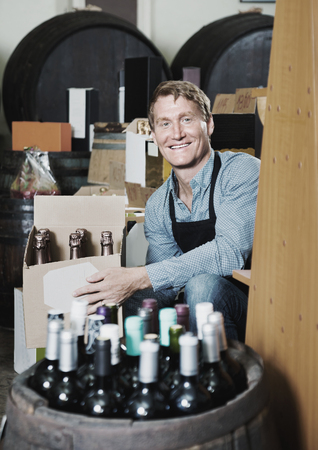 Glad smiling  man seller wearing apron having package box with wine bottles in wine store