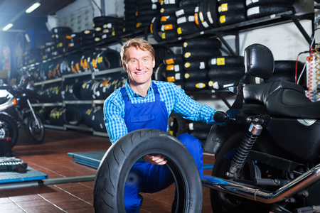 Portrait of cheerful adult man working with bike tires in tire shop